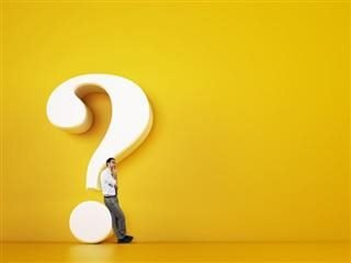 A businessman leaning against a giant statue of a question mark in a completely yellow room
