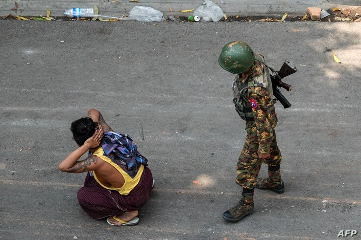 A soldier detains a man during a protest against the military coup in Mandalay, Myanmar.