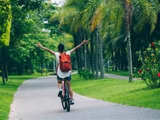 woman riding a bicycle  on a path with no hands