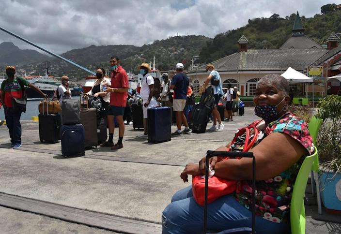 British, Canadian and U.S. nationals wait to board the Royal Caribbean cruise ship Reflection to be evacuated free of charge, in Kingstown on the eastern Caribbean island of St. Vincent, Friday, April 16, 2021.
