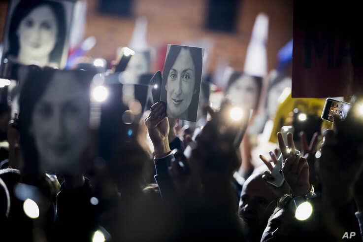 People hold pictures of slain journalist Daphne Caruana Galizia as they protest outside the office of the Maltese Prime...