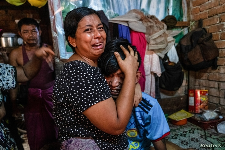 Family members cry in front of a man after he was shot dead during a crackdown on an anti-coup protesters by security forces in Yangon, Myanmar, March 27, 2021.